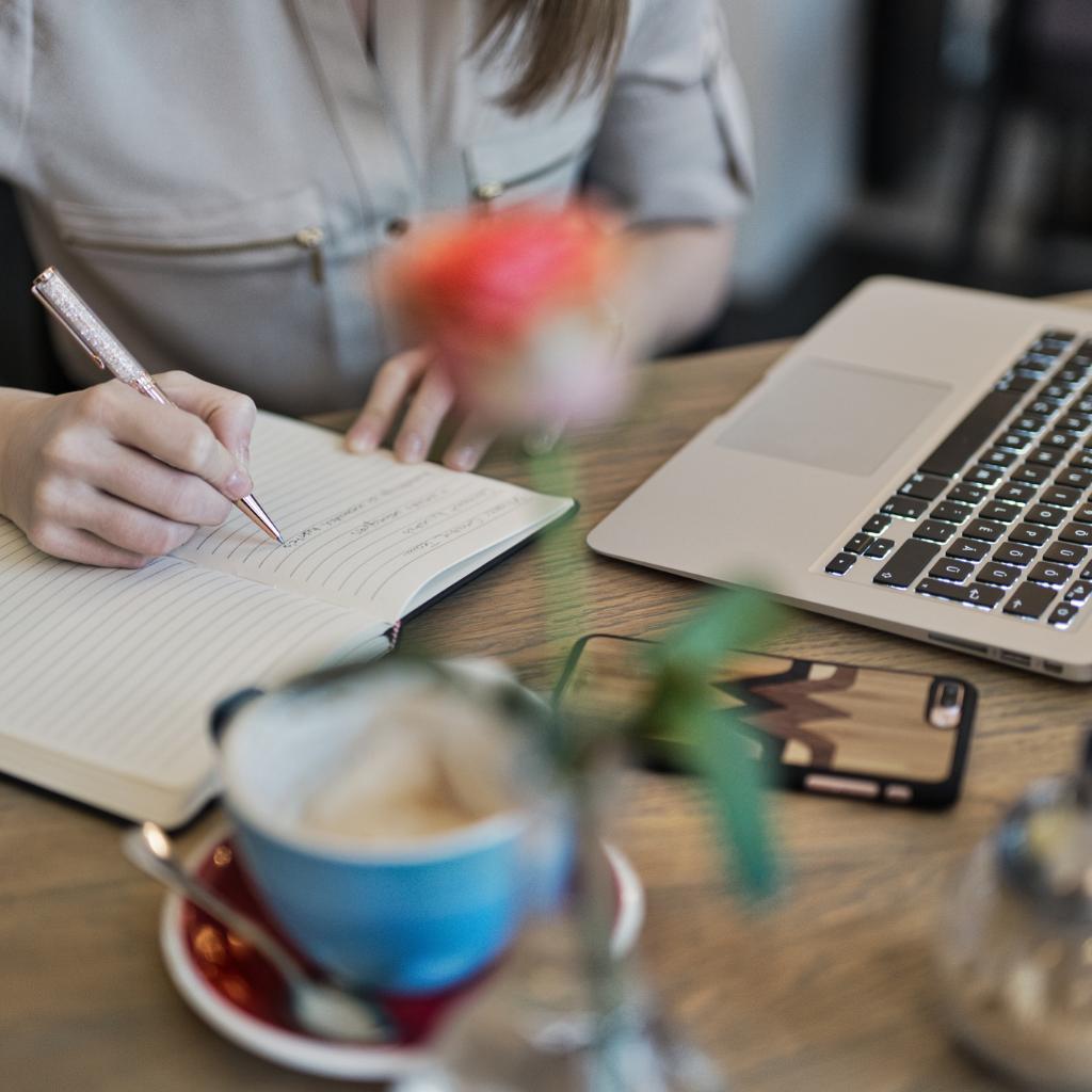 אשה במשרד כותבת ולידה מחשב עציץ וכוס קפה